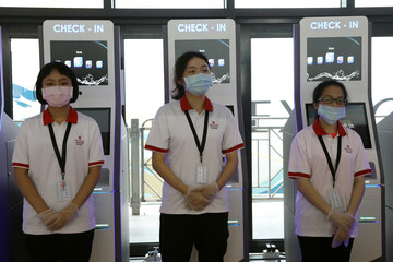 Staff wearing face masks and gloves prepare to help passengers check in at the Explorer Dream cruise ship in Keelung