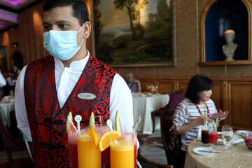 A member of the staff wears a face mask to prevent the spread of the coronavirus disease (COVID-19), at the canteen on Explorer Dream cruise ship in Keelung