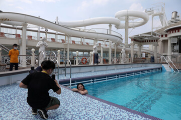 An internet show host poses in the swimming pool on the Explorer Dream cruise ship in Keelung