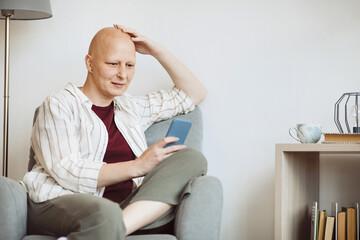 Minimal portrait of bald adult woman using smartphone and smiling while sitting in cozy armchair at home, alopecia and cancer awareness