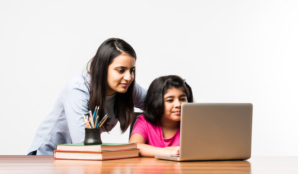 Indian / Asian little girl studying using her laptop or attending online school at home with mother