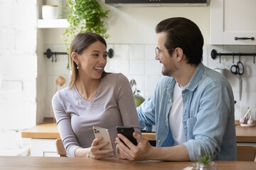 Overjoyed millennial Caucasian couple sit relax in modern home kitchen have fun using cellphones together, happy young husband and wife enjoy leisure weekend, shopping online on smartphones