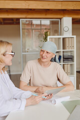 Vertical warm-toned portrait of smiling bald woman listening to female doctor showing info at digital tablet during consultation on alopecia and cancer recovery