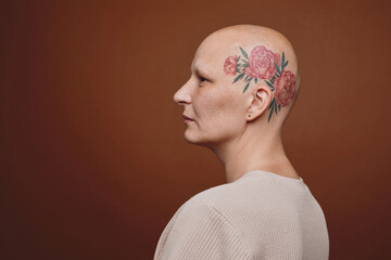 Minimal side view portrait of confident bald woman with head tattoo posing against brown background in studio, alopecia and cancer awareness, copy space