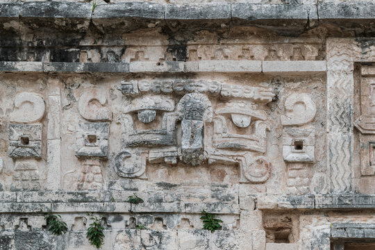 Close-up on the pre-columbian carvings on the walls of one of the building at the Chichen-Itza Mayan site, Mexico.