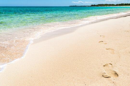 Footprints on the tropical Xcacel beach on the Caribbean Sea coast. Beautiful tropical landscape, Quintana Roo, Mexico.