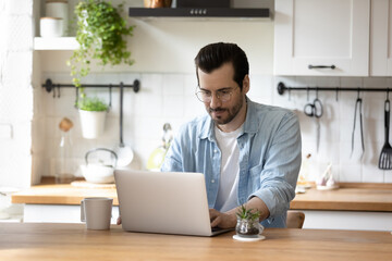 Young Caucasian male in glasses sit in kitchen work freelance on modern laptop at home, focused millennial man look at computer screen, browse surf internet on gadget, technology concept