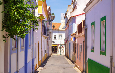 Picturesque street in Lagos, Portugal : colorful painted houses of the narrow alley way.