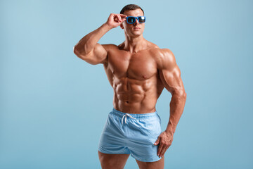 Handsome muscular man naked torso abs, isolated on blue background. Fitness male model in fashionable sunglasses