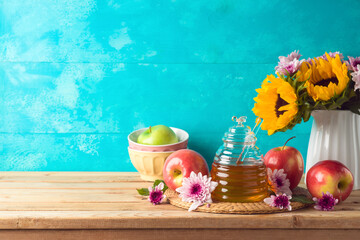 Jewish holiday Rosh Hashana background with honey jar, apple and sunflowers on wooden table
