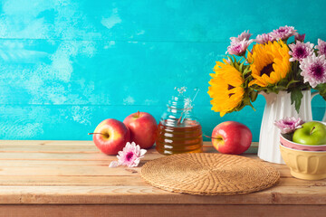 Jewish holiday Rosh Hashana background with honey jar, apples and sunflowers on wooden table. Kitchen counter with copy space for product display