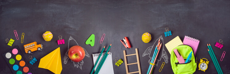 Back to school background with bag backpack, rocket sketch and school supplies over chalkboard. Top view from above