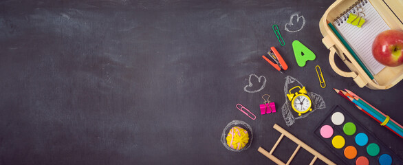 Back to school background with wooden suitcase box and school supplies over chalkboard. Top view from above