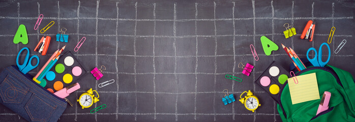 Back to school background with bag backpack, pencil case and school supplies over chalkboard. Top view from above