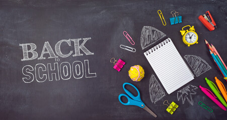 Back to school background with notebook, rocket sketch and school supplies over chalkboard. Top view from above