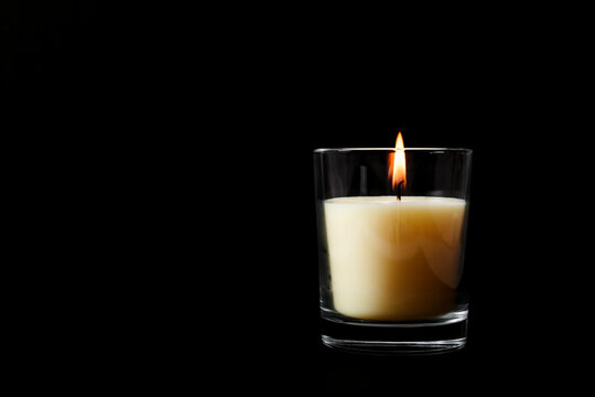 White wax burning candle in glass Isolated on black background, mock up