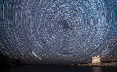 Star Trails with the neowise comet seen at La Pelosa beach, under the medieval tower in Stintino - Sassari, Sardinia