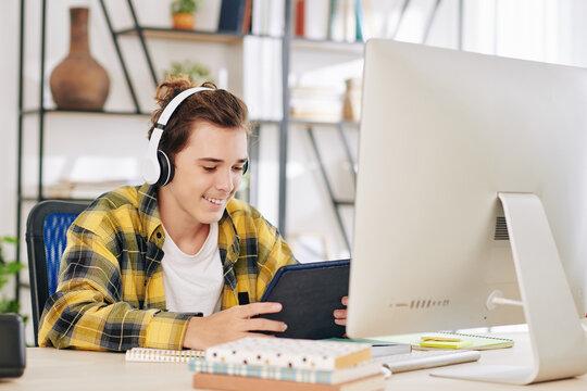 Excited teenage boy in headphones watching tv series on tablet computer instead of doing homework on computer