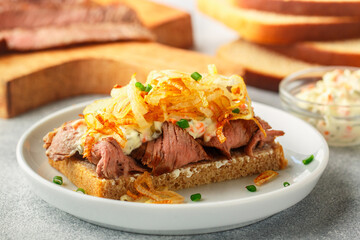 Rye bread sandwich with roast beef, fried onions, mayonnaise and remoulade sauce. Danish gourmet snacks