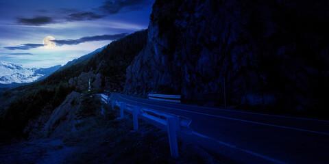 mountain road in fagaras ridge at night. popular travel destination in full moon light. wide serpentine. summer morning scenery