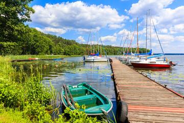Obraz Fishing boat and yacht boats at pier on lake shore in Karwica village port on sunny summer day, Mazury Lake District, Poland - fototapety do salonu