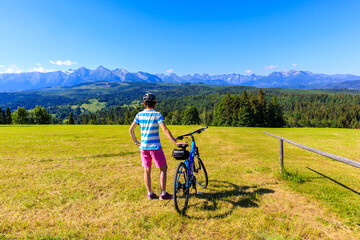 Young female biker standing with bicycle on meadow and looking at panorama of Tatra Mountains on beautiful summer sunny day at Lapszanka Pass, Poland