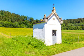 Old chapel on green meadow in Osturnia village in Tatra Mountains on beautiful summer sunny day, Slovakia