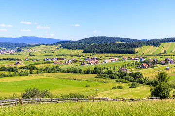 Green farming fields and view of Kacwin village in Tatra Mountains on beautiful summer sunny day, Poland