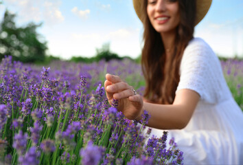 Young woman in lavender field on summer day, focus on hand