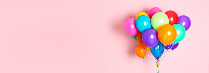 Fototapeta Bunch of bright balloons on pink background, space for text. Banner design obraz