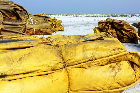 Containment boom on white sand beach ready for oil spill cleanup.