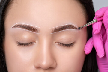 Brunette teenager girl having permanent makeup tattoo on her eyebrows. Make-up artist makes...