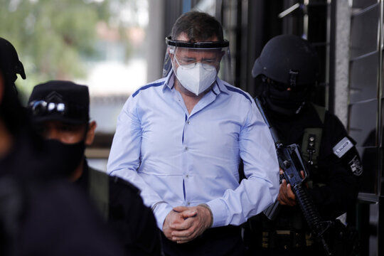 El Salvador's former Minister of Defense David Munguia Payes leaves the courthouse after his detention on suspicion of unlawful association and other crimes linked to the arrangement of a 2012-2014 truce between crime gangs in San Salvador