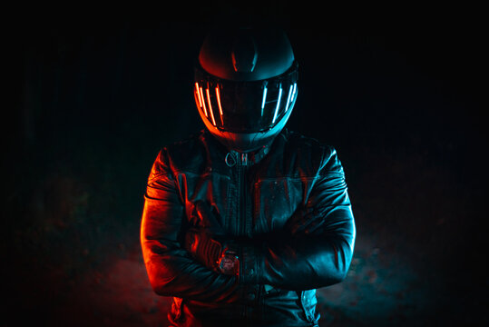 motorcyclist with black helmet at night and crossed arms