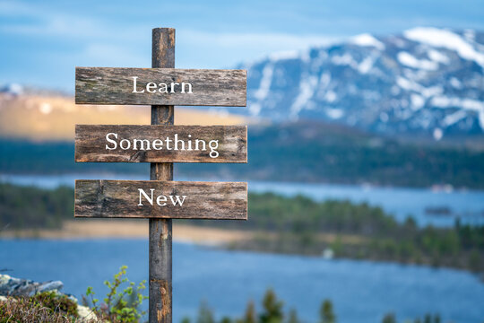 learn something new text on wooden signpost outdoors in landscape scenery during blue hour. Sunset light, lake and snow capped mountains in the back.