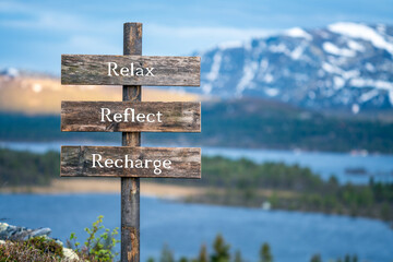 Fototapeta relax reflect recharge text on wooden signpost outdoors in landscape scenery during blue hour. Sunset light, lake and snow capped mountains in the back. obraz
