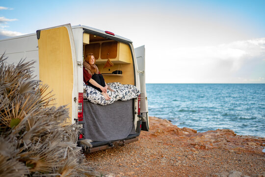 Thoughtful woman sitting in motor home at beach against sky