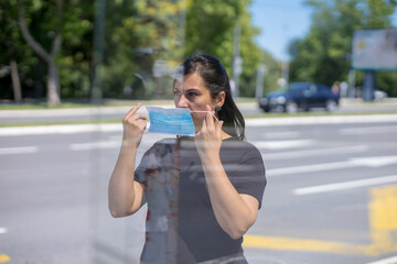 woman at bus stop putting mask on her face