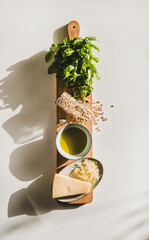Ingredients for cooking Italian Pesto sauce. Flat-lay of fresh basil leaves, olive oil, pine nuts, garlic, Parmesan cheese on rustic board over white background, top view, vertical composition