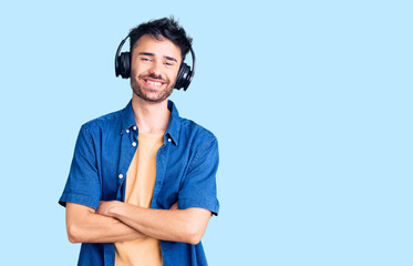 Young hispanic man listening to music using headphones happy face smiling with crossed arms looking...