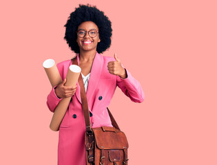 Young african american woman holding architect blueprints smiling happy and positive, thumb up doing excellent and approval sign