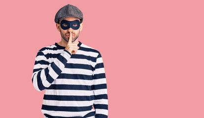 Young handsome man wearing burglar mask asking to be quiet with finger on lips. silence and secret concept.