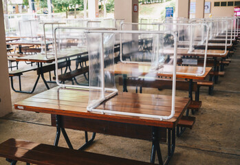 Group of plastic partition setting on table in canteen for reduce and protection the COVID-19 virus spreads in pandemic. Social distancing concept.