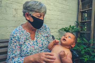Grandmother with face mask holding her baby grandchild