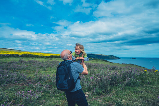 Grandfather liftingh his preschooler grandchild in a meadow