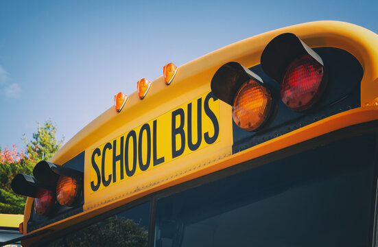 Top of a yellow school bus with lights and text. Closeup against blue sky in the fall. Back to school concept. Copy space.