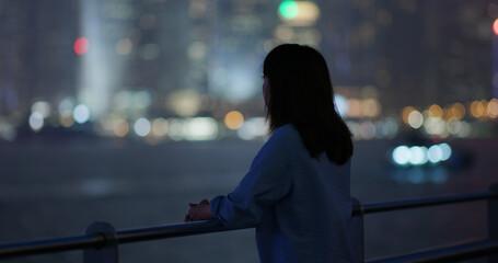 Wall Mural - Woman look at the city at night