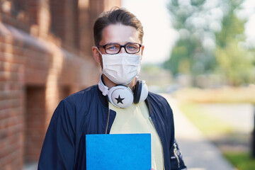 Male student in the campus wearing maskk due to coronavirus pandemic