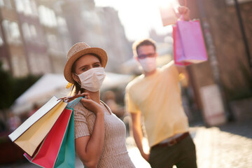 A picture of couple with shopping bags and protective masks