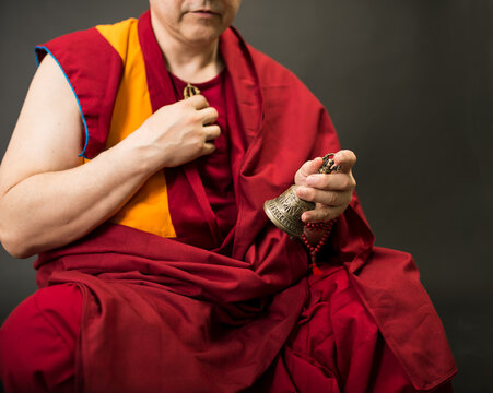 Tibetan Buddhist monk teacher in a burgundy yellow outfit suit